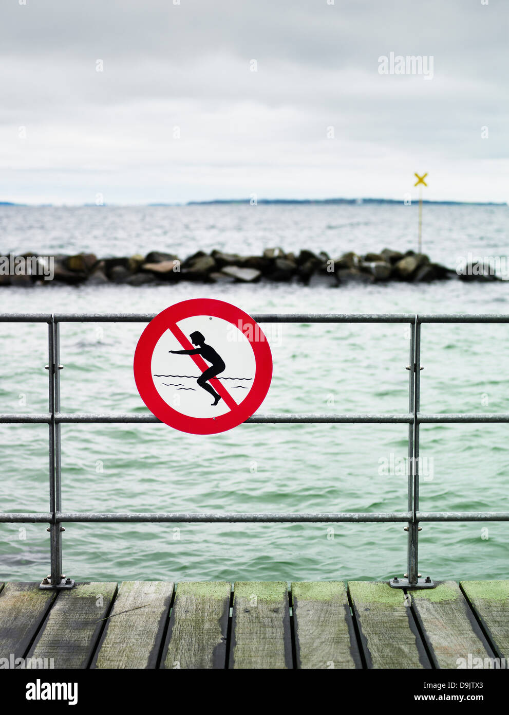 No swimming sign on pier railing - Stock Image