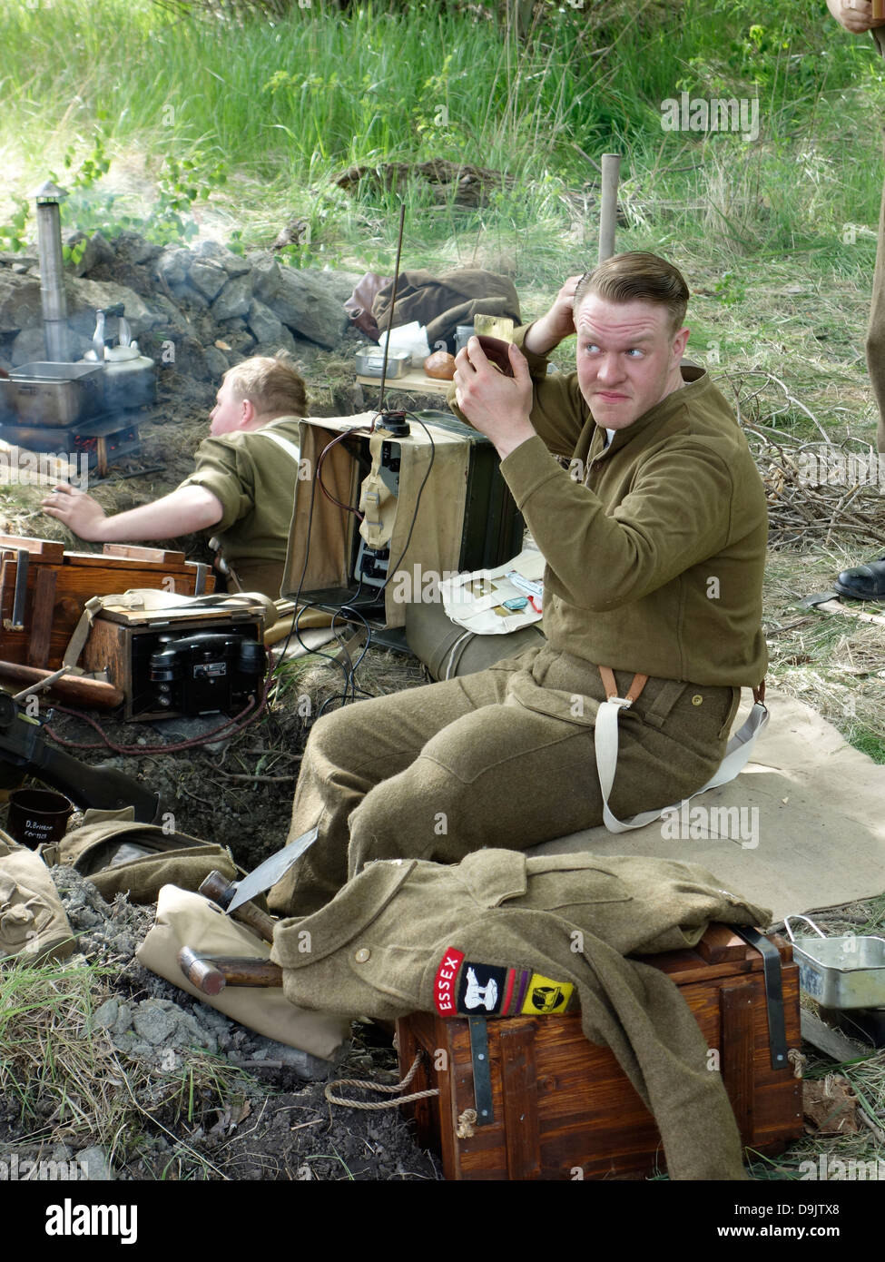 Historical re-enactment of ww2. British soldier in the trench finds time to comb his hair. - Stock Image