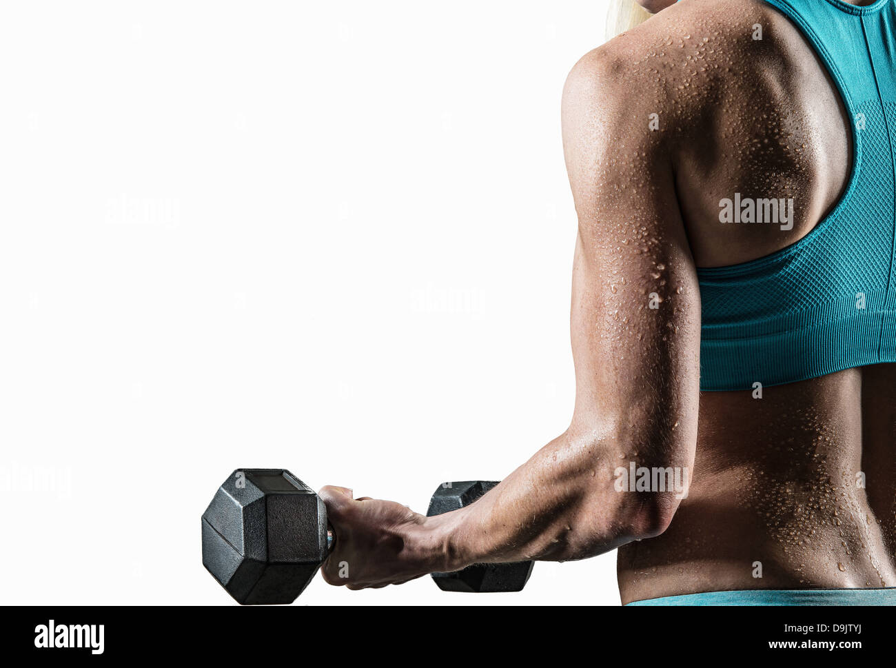 Young woman performing bicep curls, close up - Stock Image
