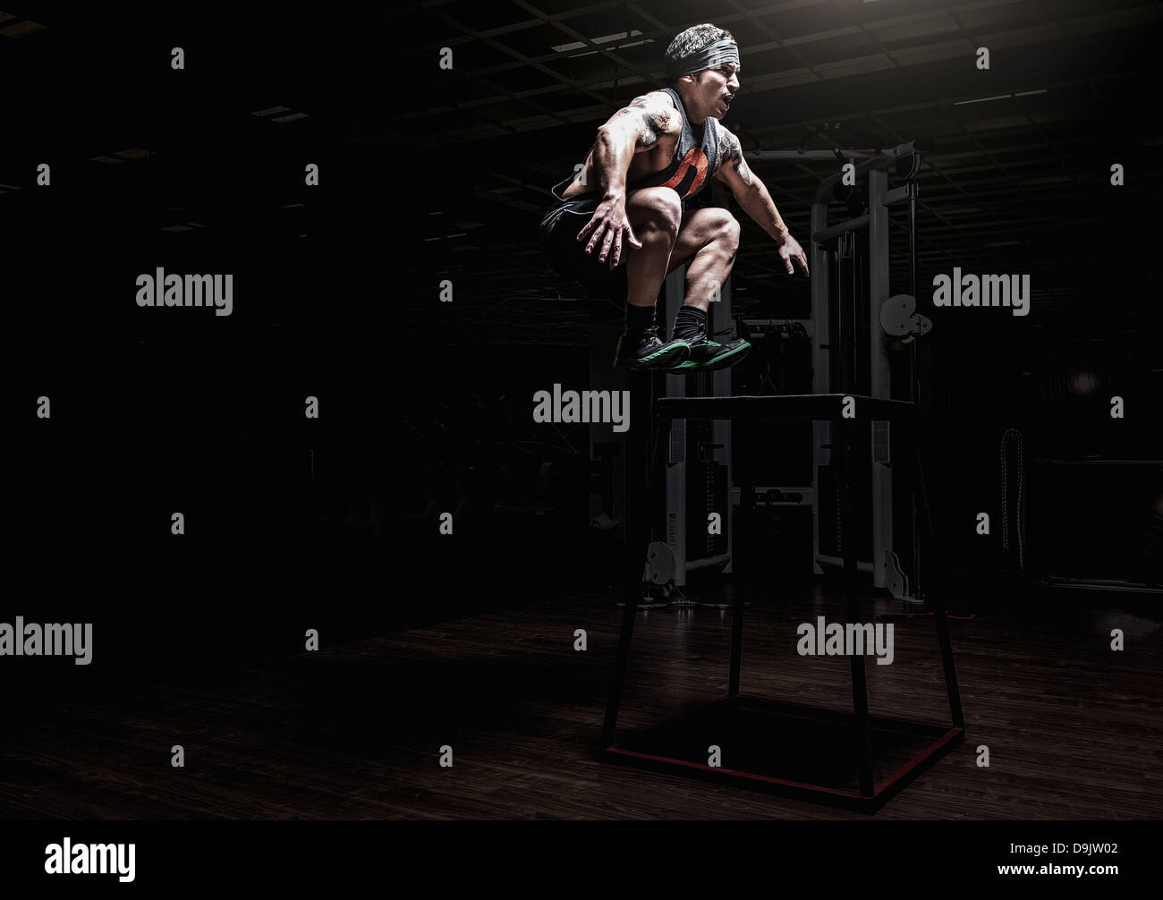 Young man leaping in gym - Stock Image