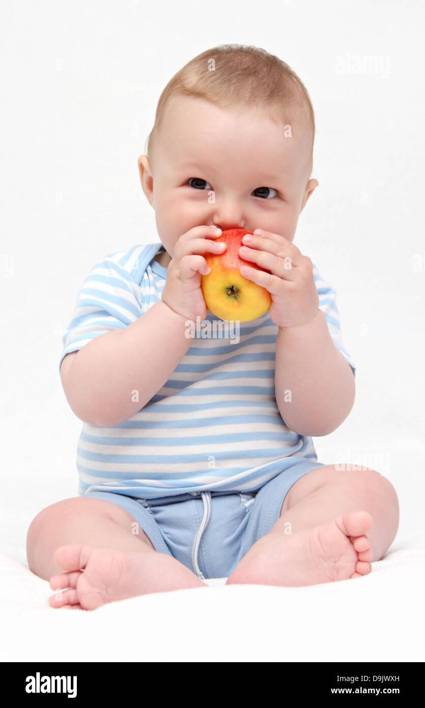 baby eating apple - Stock Image