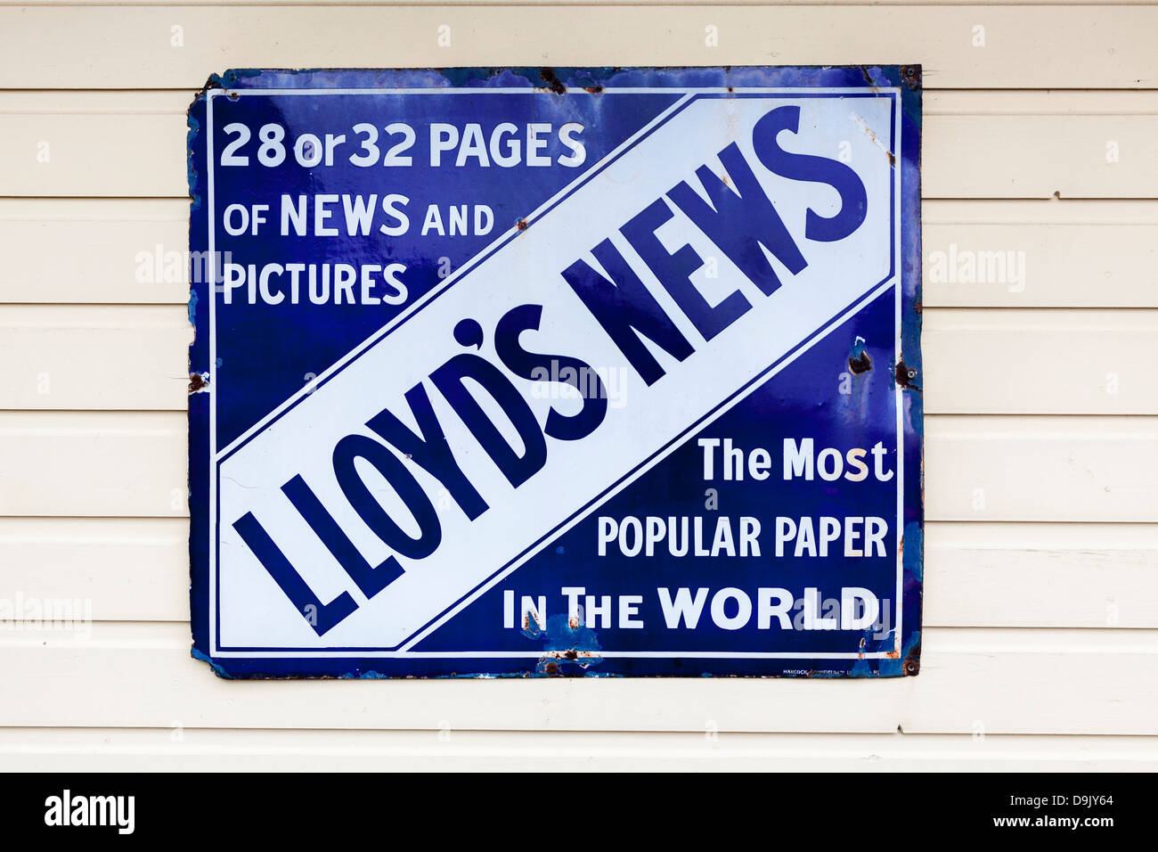 Vintage blue and white enamel sign advertising Lloyd's News, attached to wooden boards - Stock Image