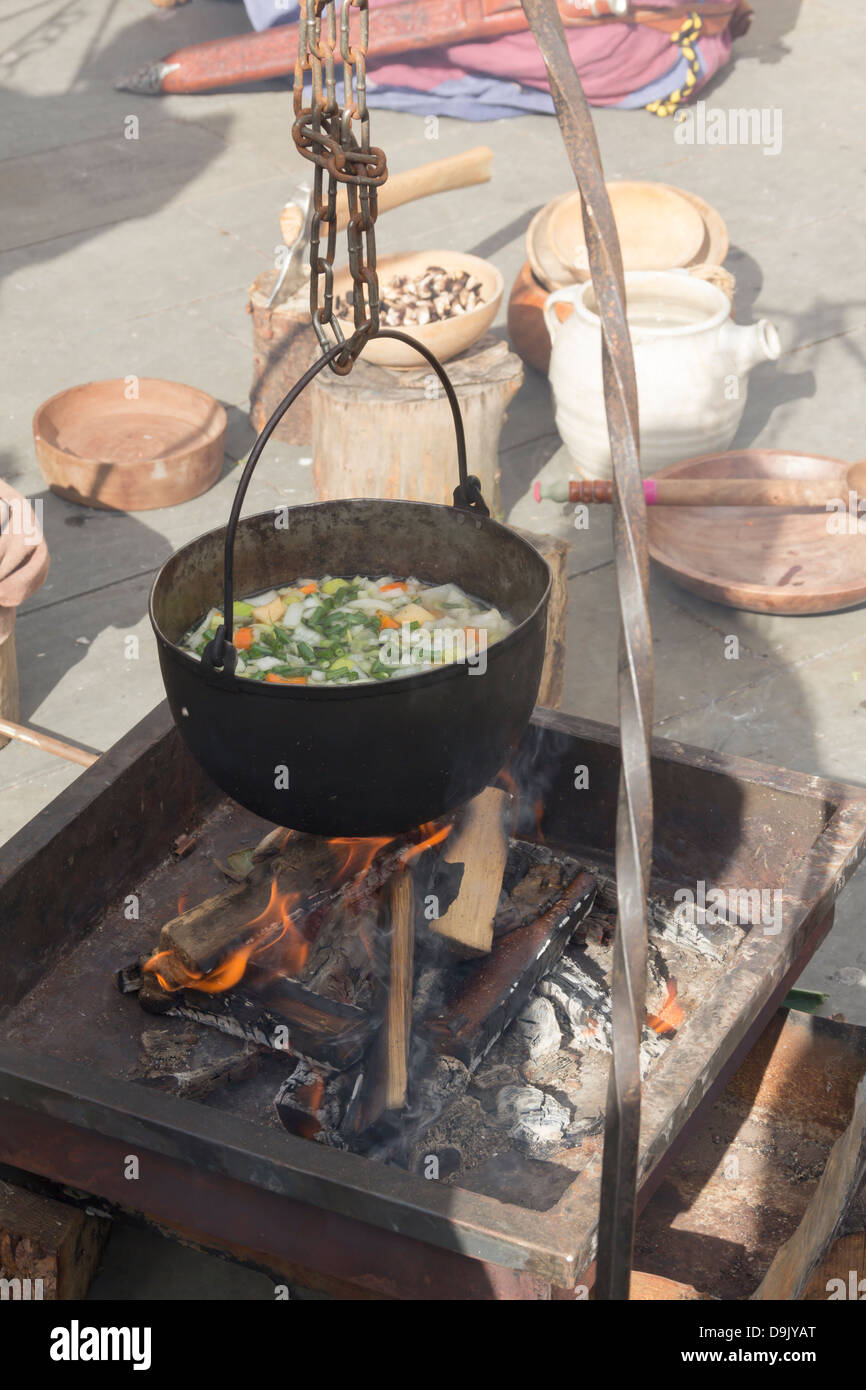 Vegetable soup being cooked by Viking reenactors in an open cooking pot over a wood fire at a Viking reenactment - Stock Image