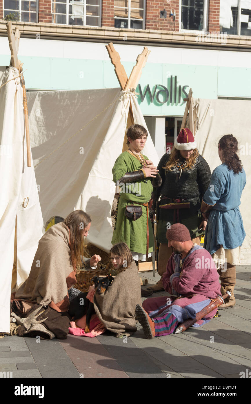 Viking reenactors including a family and a dog in the middle of the tent encampment at a  Viking reenactment event - Stock Image