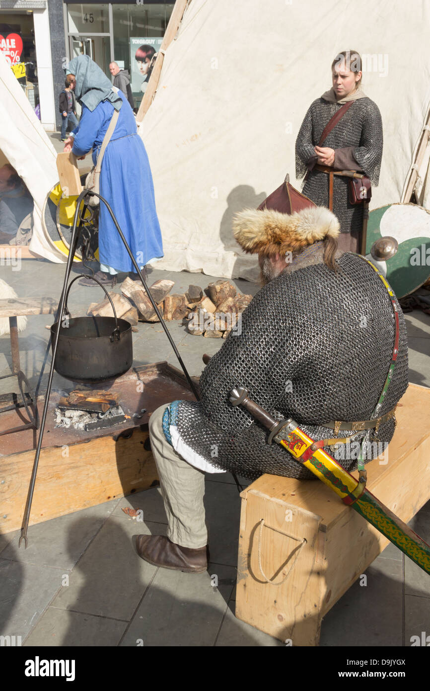 Viking reenactors and an open cooking pot over a wood fire in the middle of the tent encampment at the Viking reenactment - Stock Image