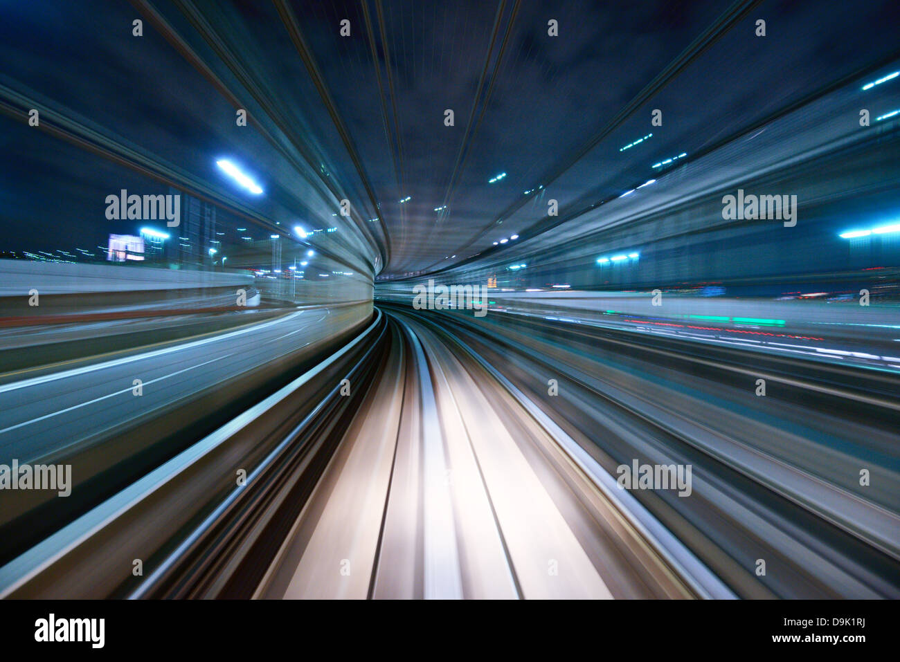 Motion blur of a city and tunnel from inside a moving monorail in Tokyo. - Stock Image