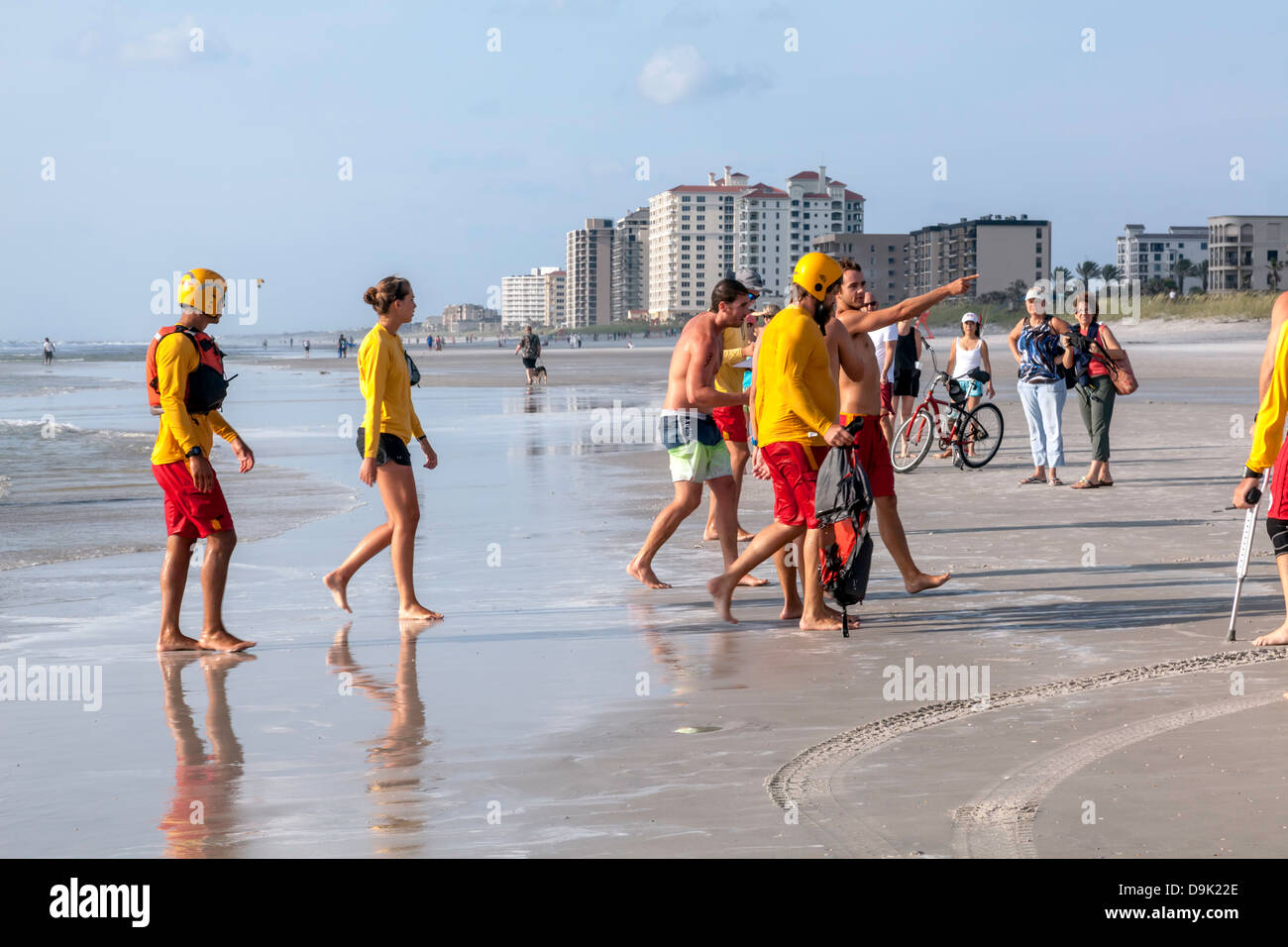 Injured competitor being escorted from ocean by beach rescue volunteer at the 4th Annual JAX Beach Paddling Challenge - Stock Image