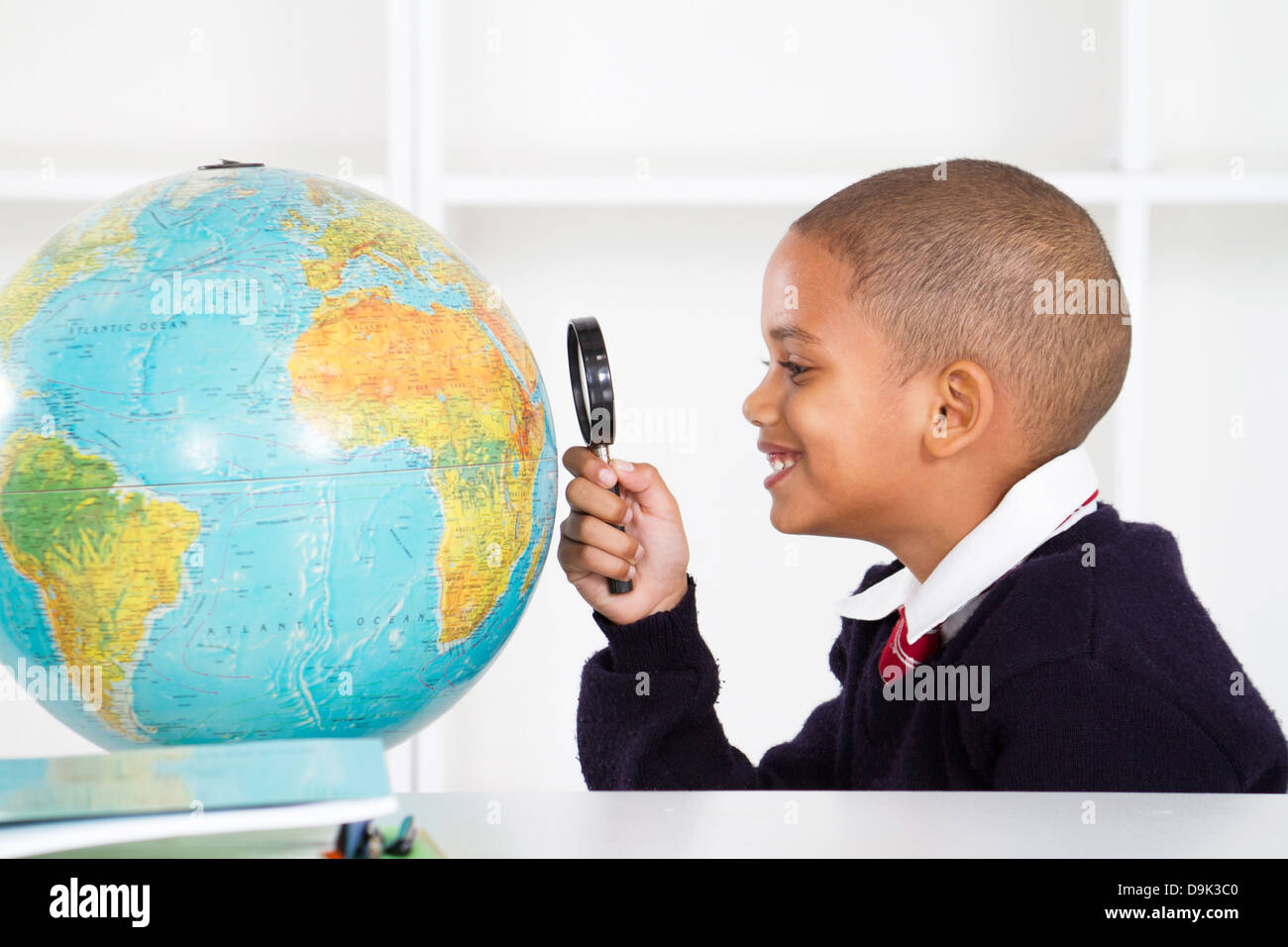 primary schoolboy using magnifying glass looking at globe - Stock Image