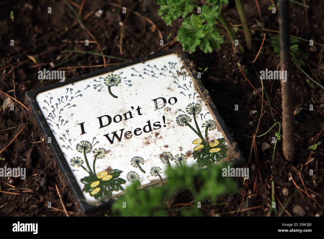 sign plaque weeds garden work plant flower - Stock Image