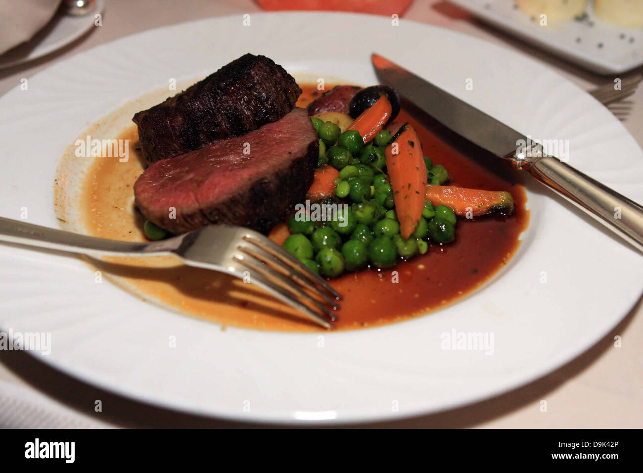 dinner supper meal food eat steak meat rare fresh peas carrots knife fork plate - Stock Image