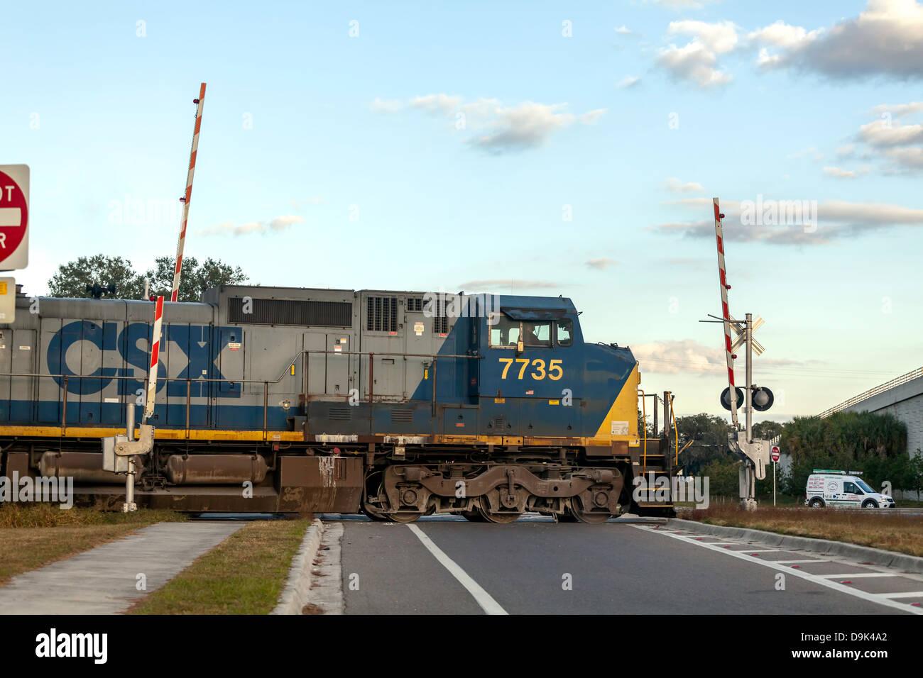 CSX engine 7735 pulling a freight train through a railroad