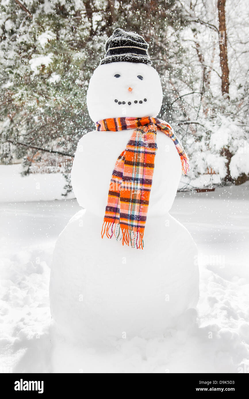Merry White Snowman with an orange scarf and a hat - Stock Image