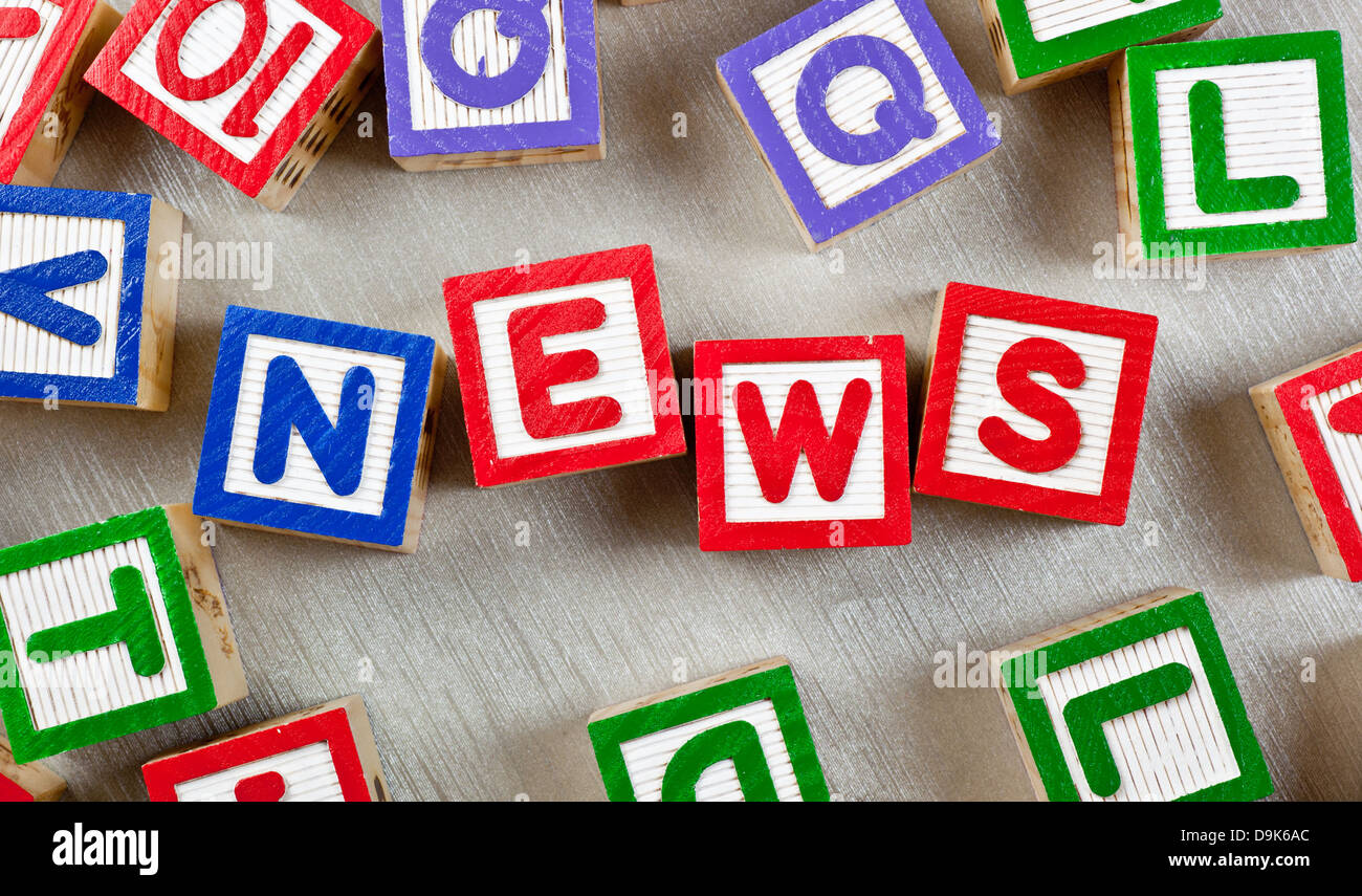 Wooden blocks forming the word NEWS in the center - Stock Image