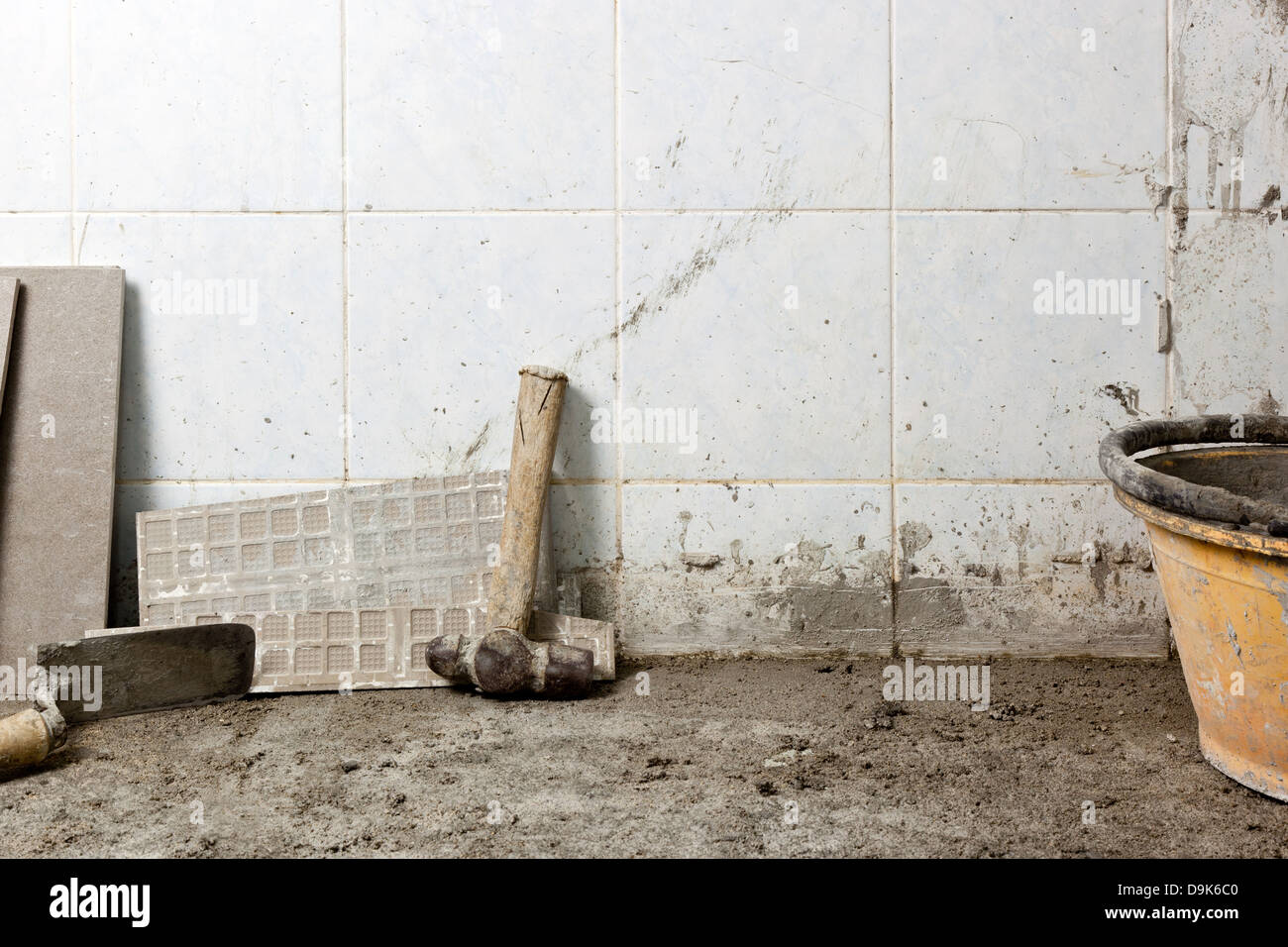 Section of the floor of a house under renovation showing the concrete subfloor and some tools - Stock Image