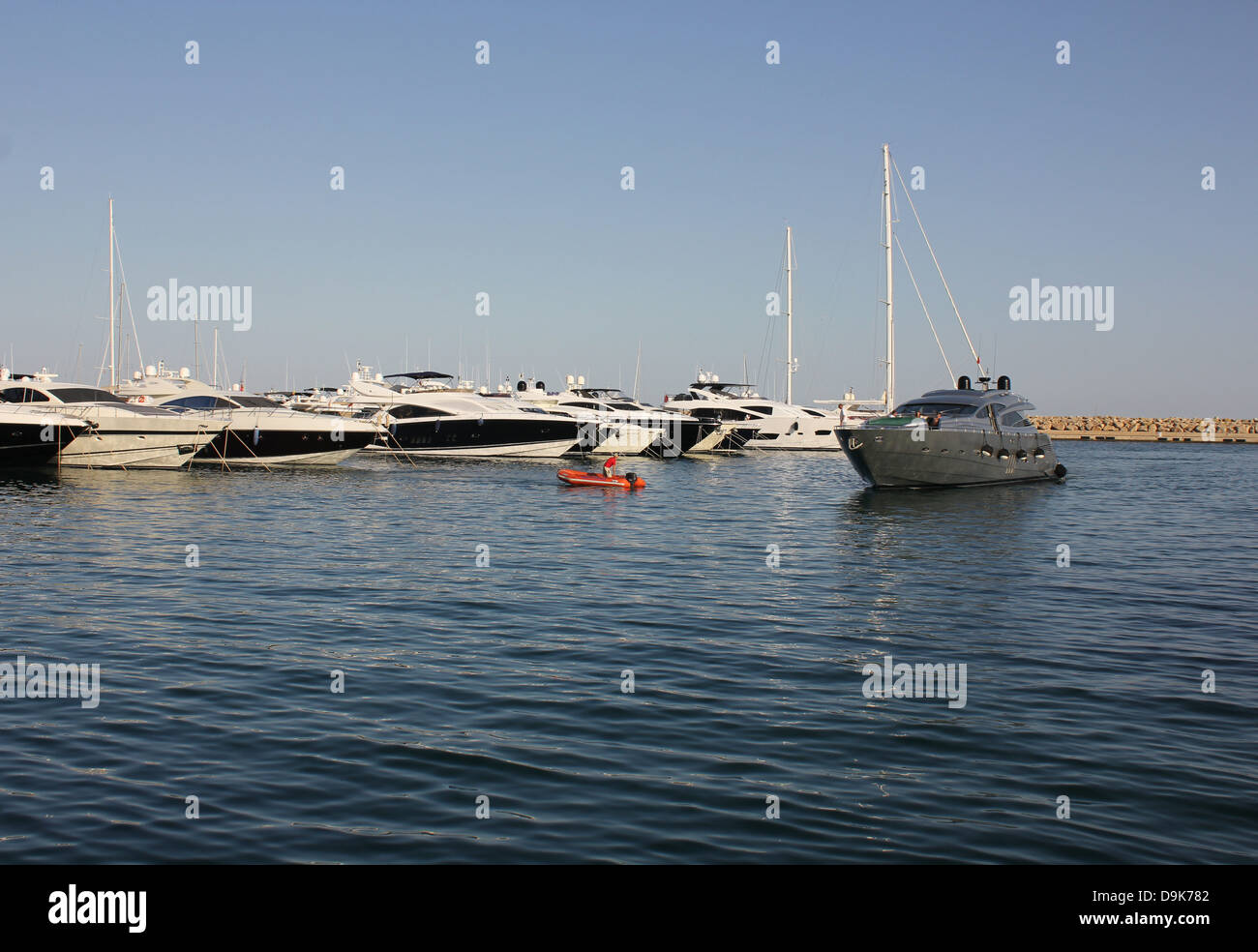 Luxury motor superyacht returning to berth - with marina berthing RIB in attendance - in Puerto Portals marina, - Stock Image