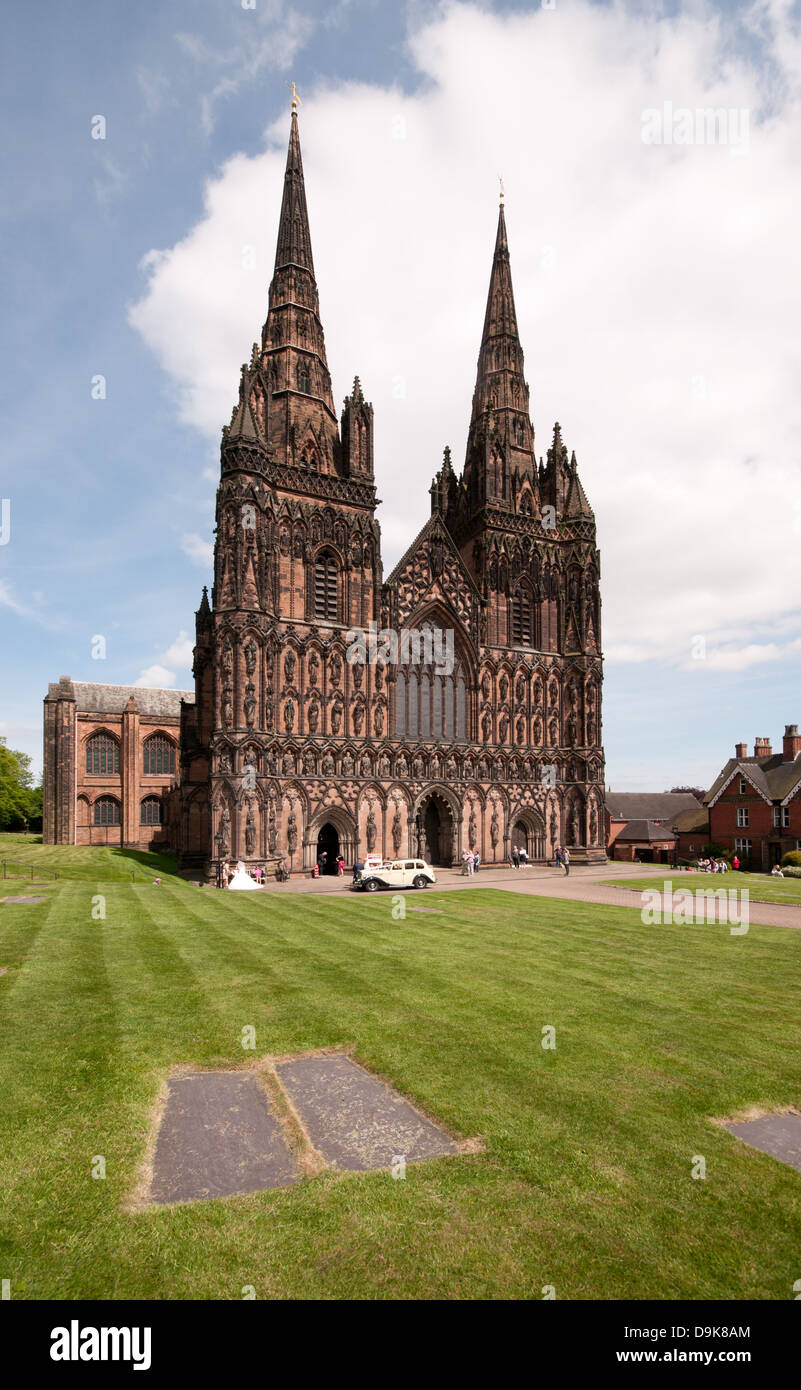 West front of Lichfield Cathedral of St Chad with vintage Wolsley wedding car and bride in white dress Tombstone - Stock Image