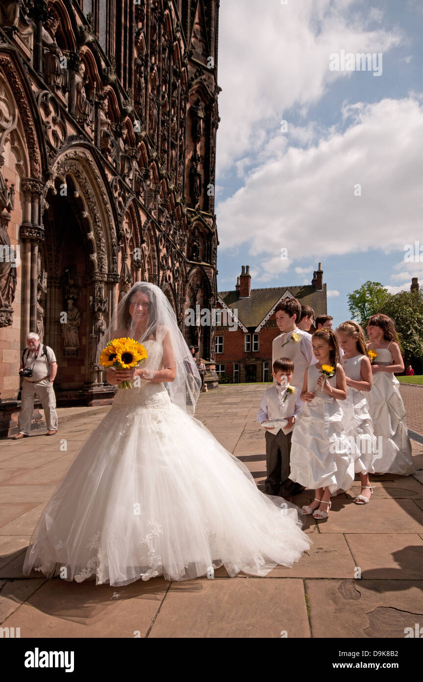 Bride in white wedding dress at west front of Lichfield Cathedral of St Chad with pages and flower girls - Stock Image