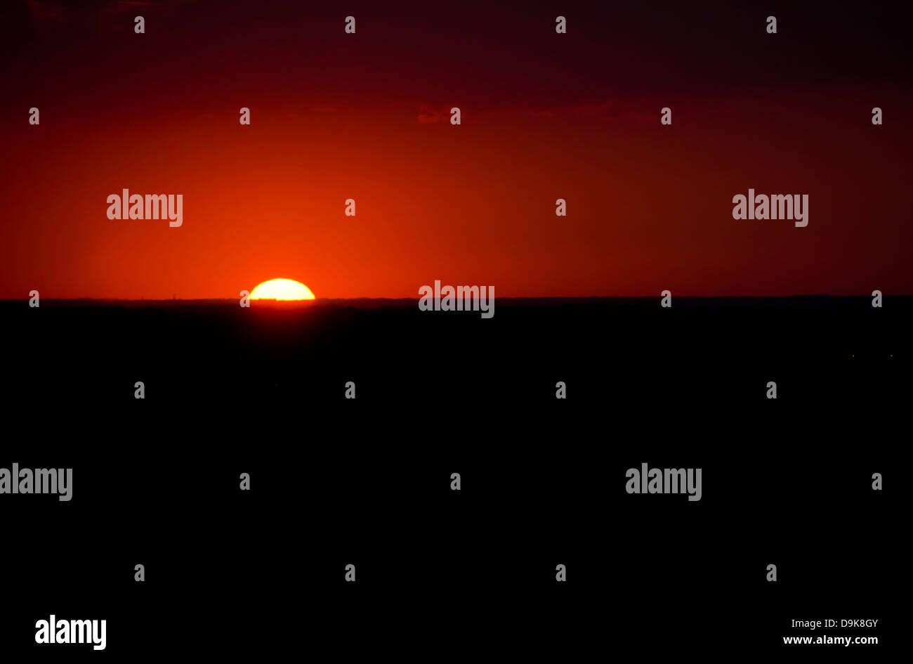 Intense red dark sky illuminated by the setting sun on the horizon. - Stock Image