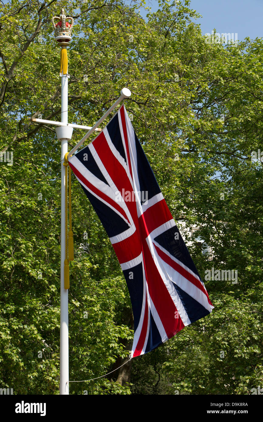 A Union Jack flying on a flagpole with a crown on the top. - Stock Image