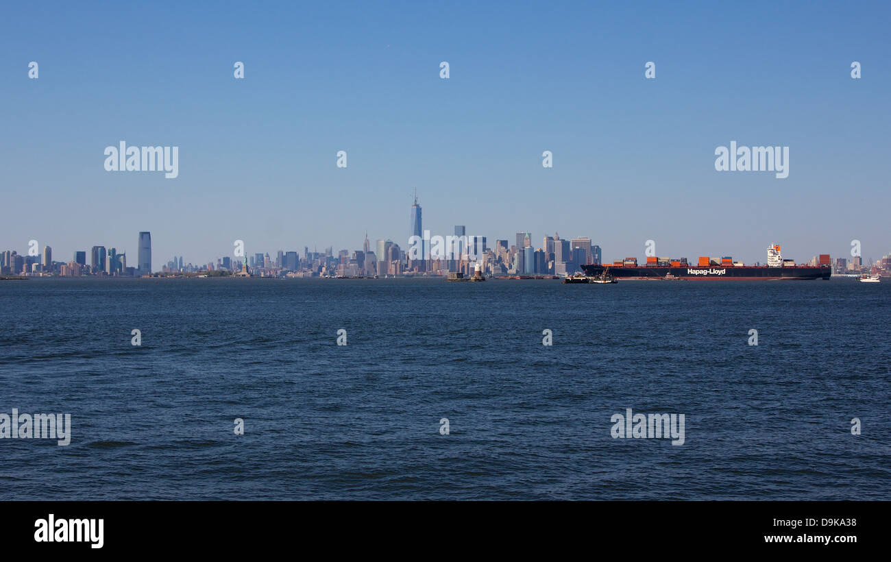 NEW YORK, NY, USA - MAY 27, 2013: A German container ship arrives at New York City before the backdrop of the Manhattan - Stock Image