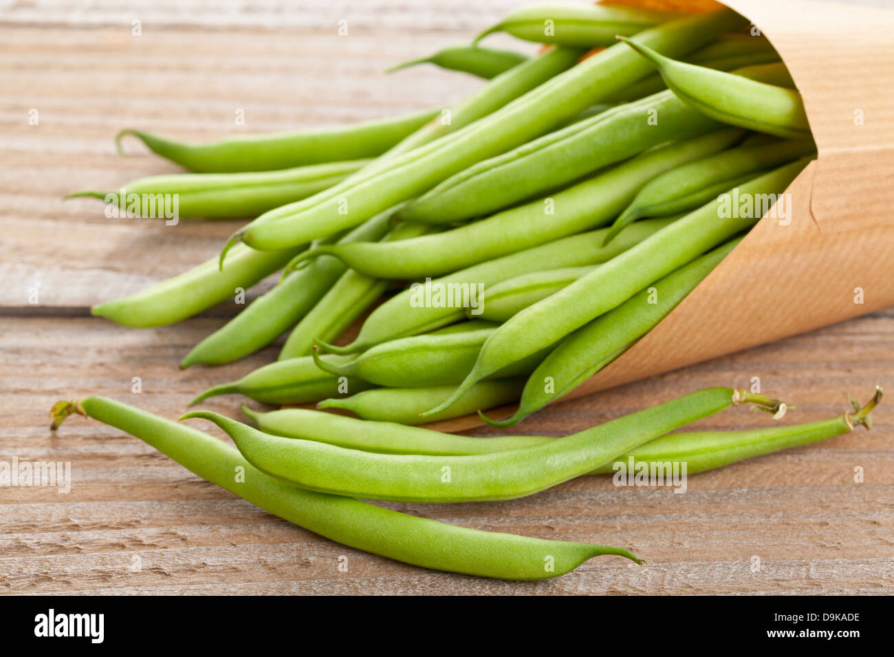 Organic pole beans in paper bag on wooden table - Stock Image