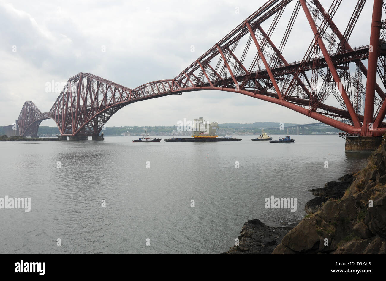 The Forth, near Edinburgh, UK. 21st June, 2013. Final piece of new aircraft carrier entering under the Forth Bridge - Stock Image