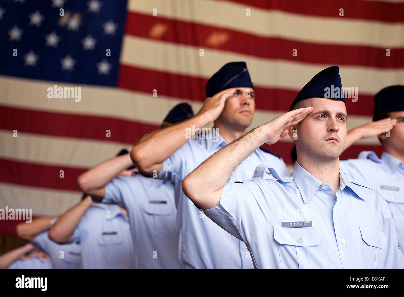 US Air Force Airmen salute to the American flag during the singing of the Star Spangled Banner a change of command - Stock Image