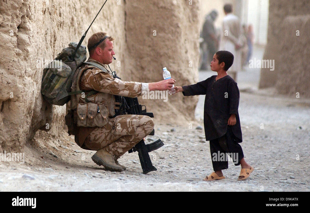 British Royal Air Force Airman Joe Ralph hands a bottle of water to a local child during an International Security - Stock Image