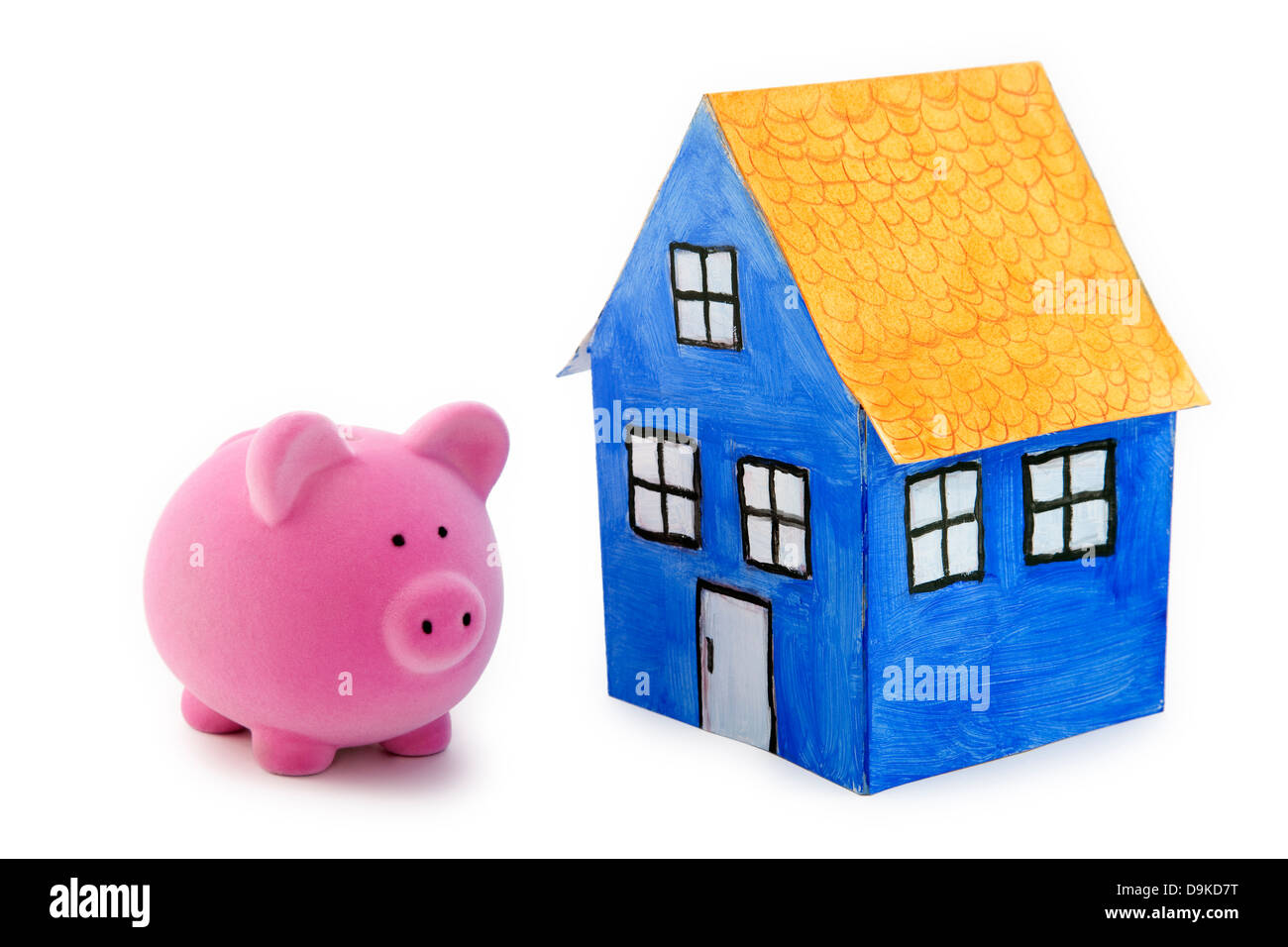 Piggy bank and blue paper house with clipping path - Stock Image