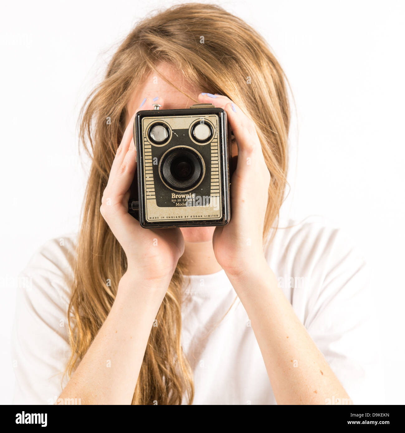 A young woman with long blonde hair holding using an old Kodak Box Brownie camera - Stock Image