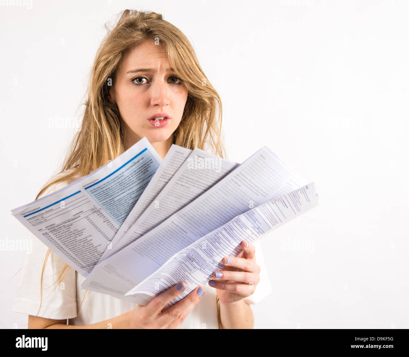 A young woman with long blonde hair worried about paying her household utility bills - Stock Image