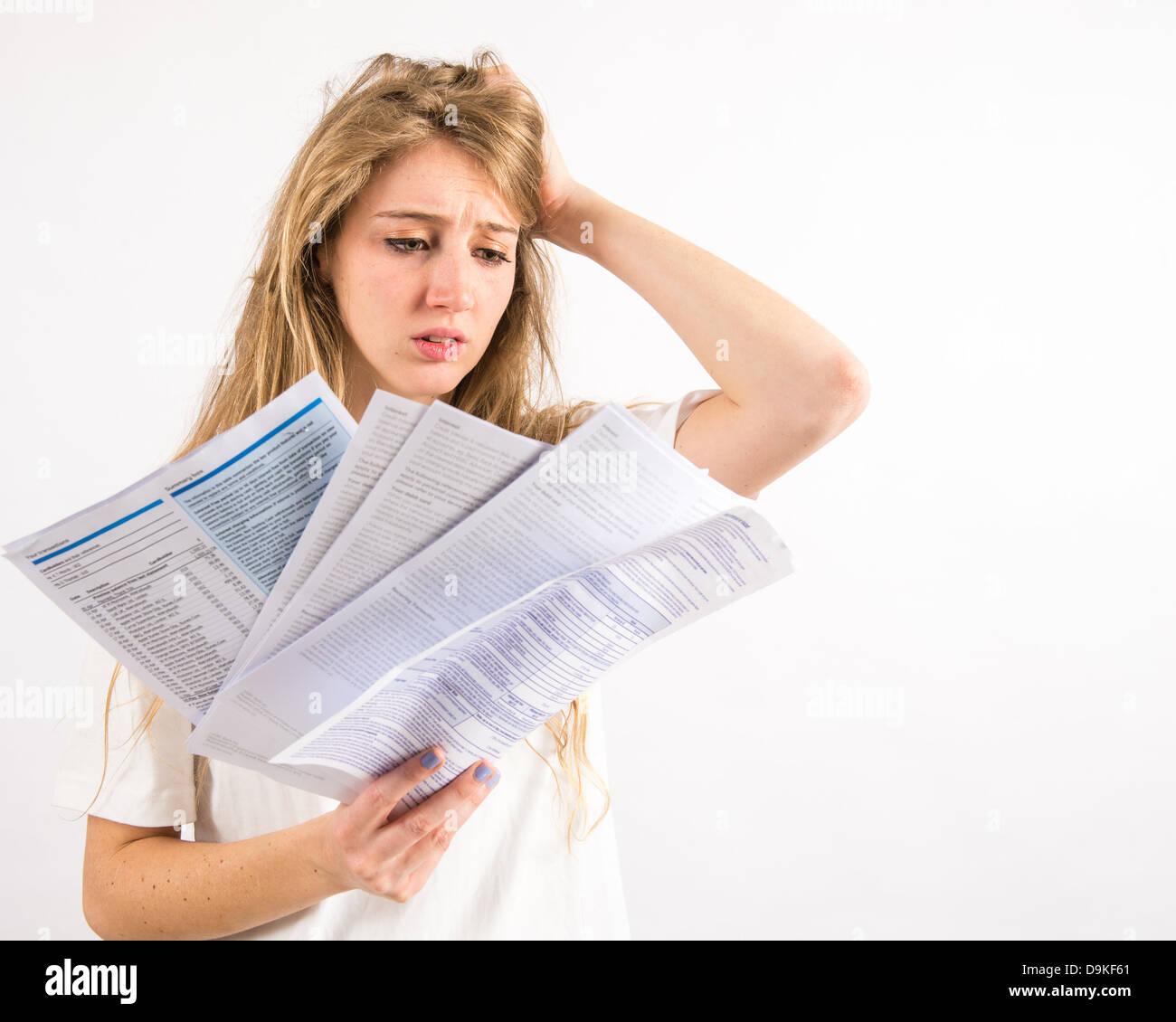 A young woman with long blonde hair worried about paying her household utility bills - money worries - Stock Image