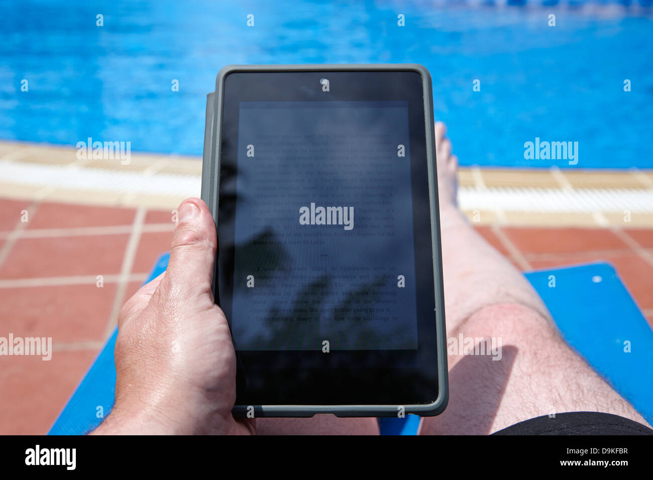 man reading ebook on tablet computer by the side of a swimming pool on holiday salou costa daurada spain - Stock Image