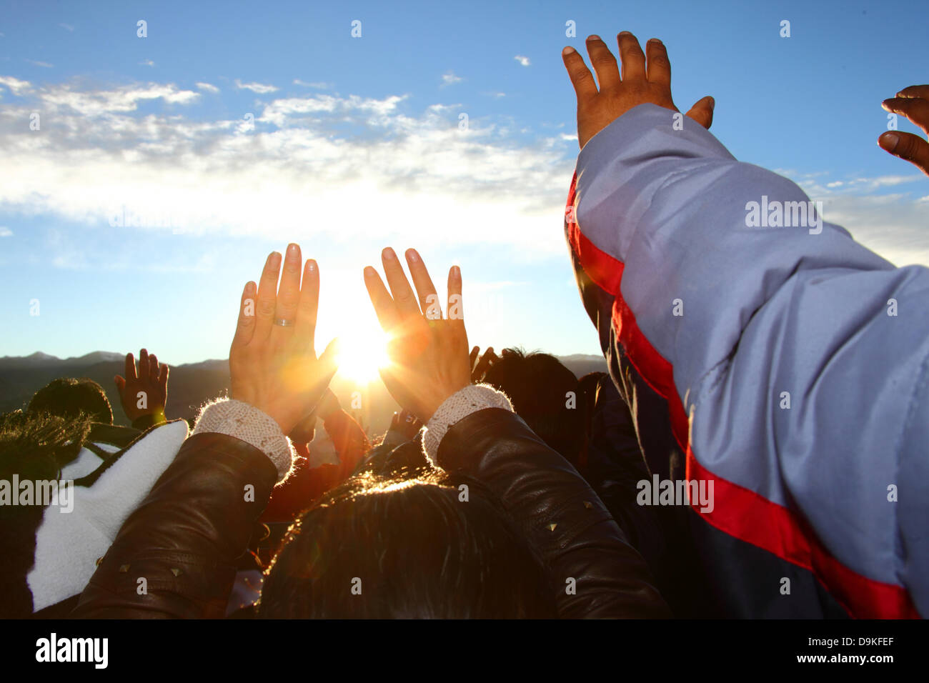 LA PAZ, BOLIVIA, 21st June. Bolivians hold up their hands to receive the warmth and energy of the rising sun at Stock Photo