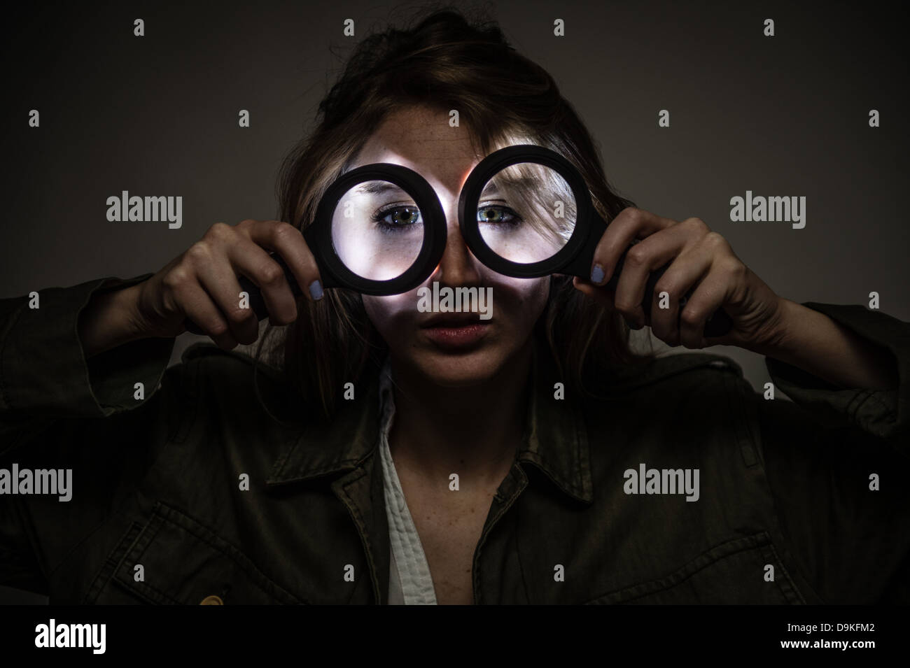 A woman holding a pair of illuminated magnifying glasses over her eyes - Stock Image