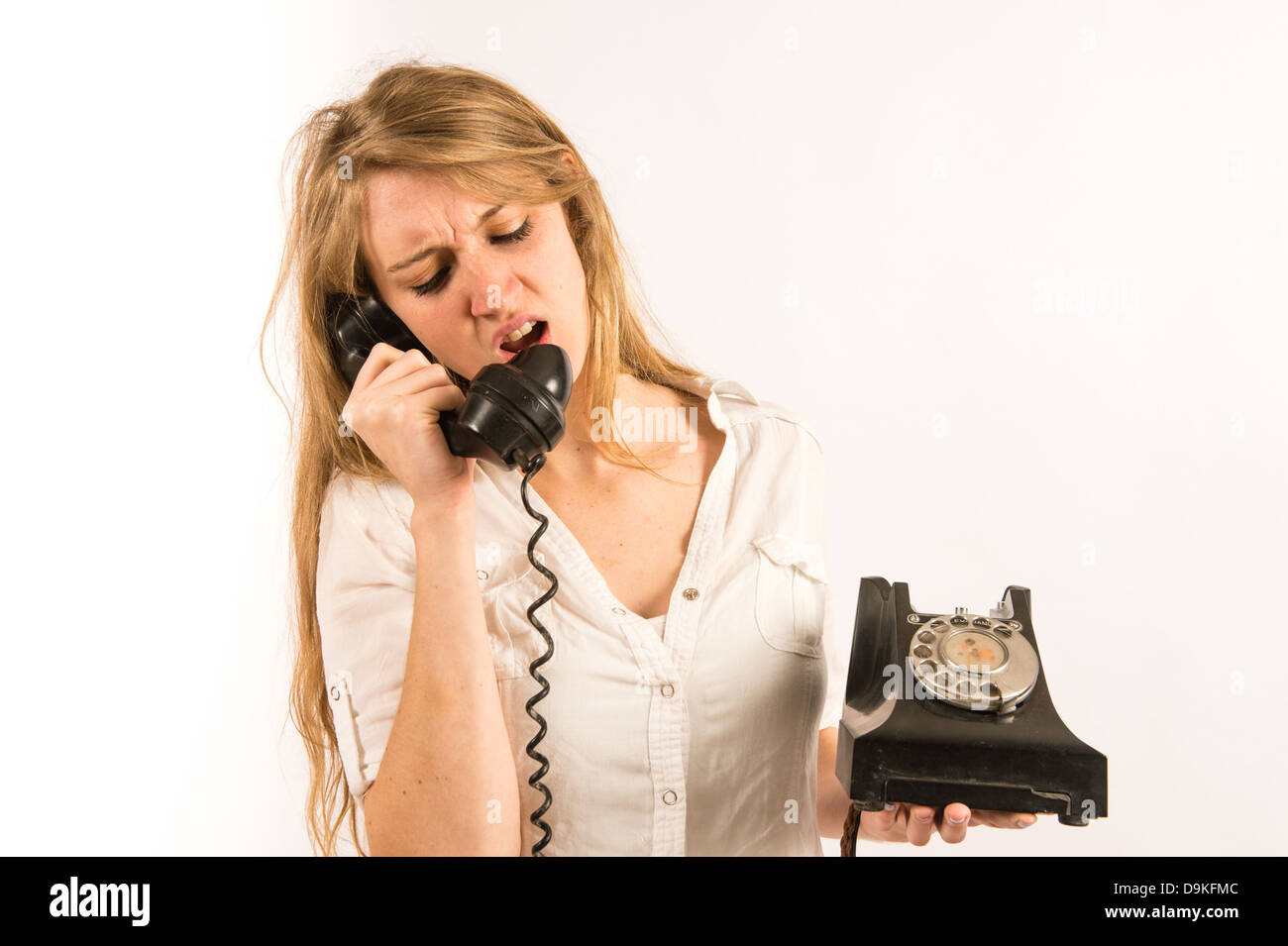 Poor customer service: An angry young woman shouting yelling into an old retro telephone receiver - Stock Image