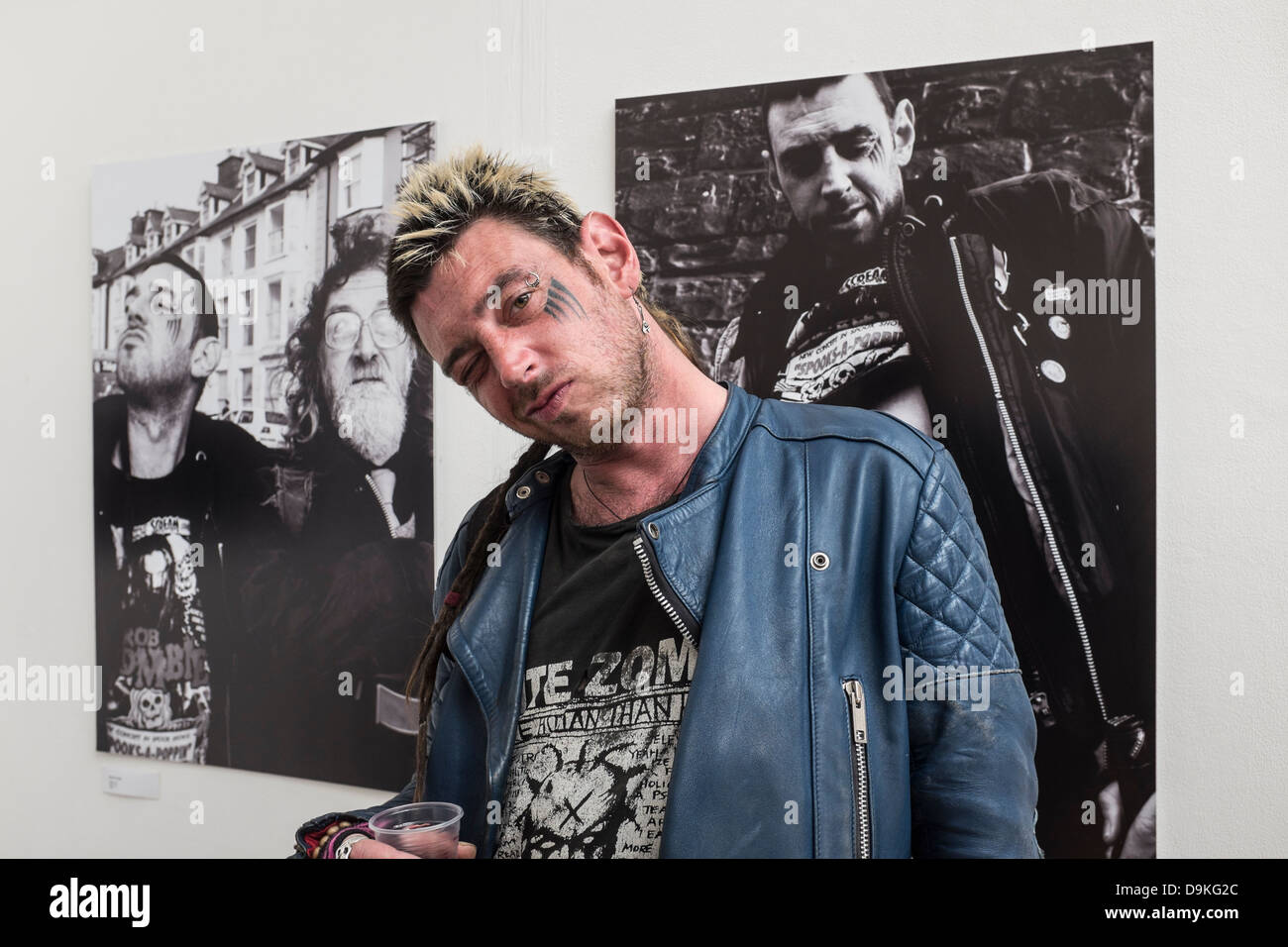 A punk style man standing in from of photos of himself at Final degree exhibition at Aberystwyth University School - Stock Image