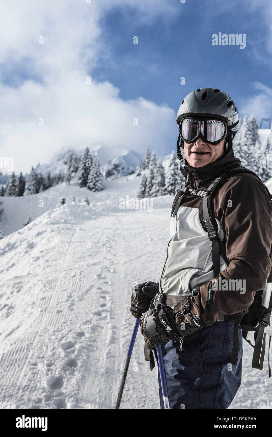 Portrait of mature man hiking in wintry landscape - Stock Image