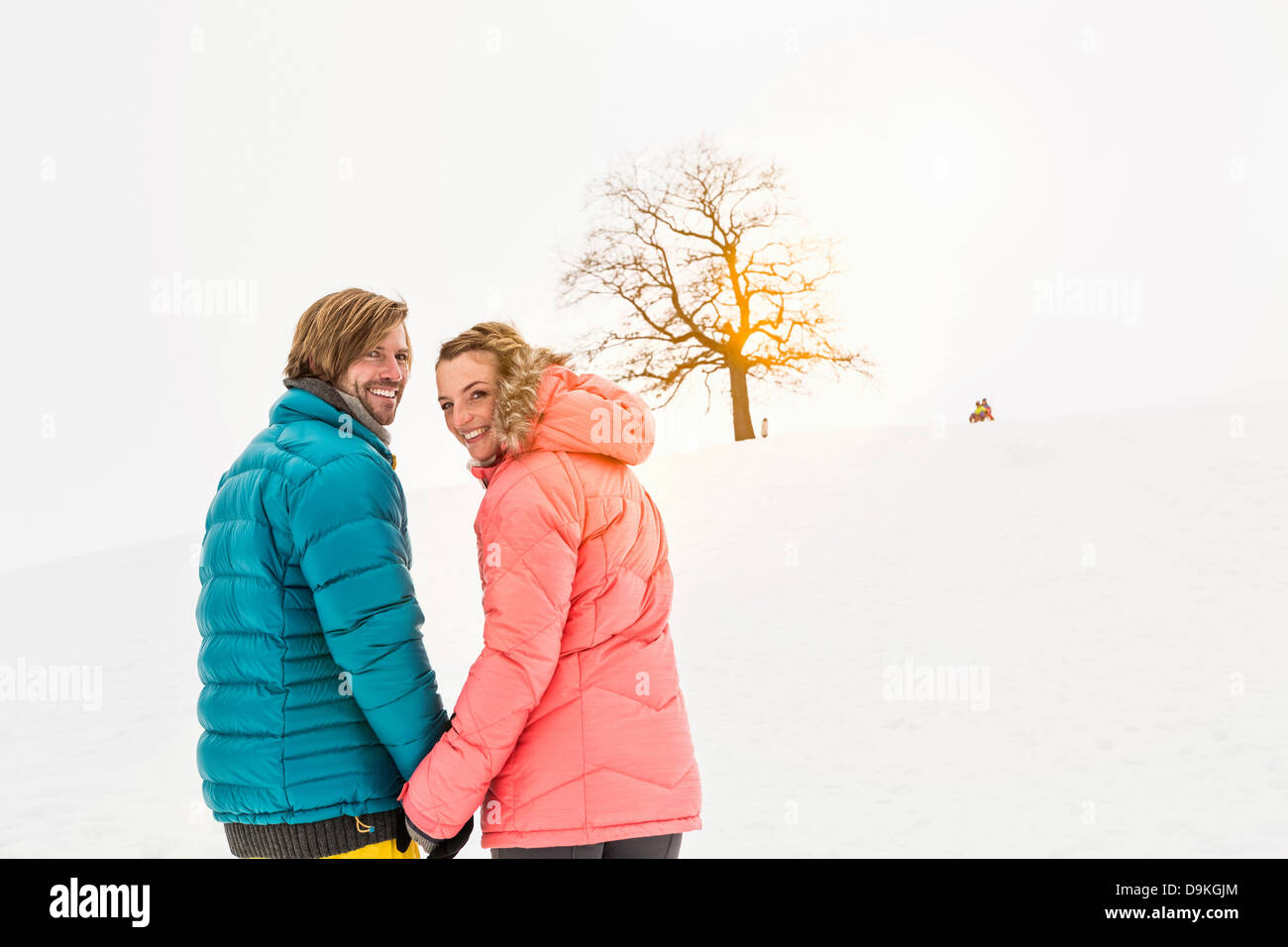 Mid adult couple walking in snow, looking over shoulder - Stock Image