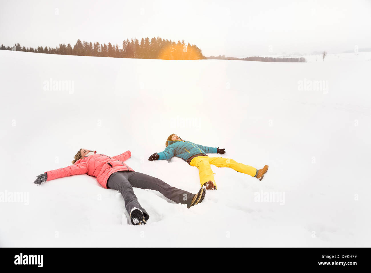 Couple making snow angels - Stock Image