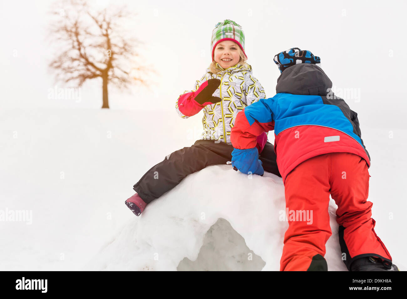 Two children on top of igloo - Stock Image