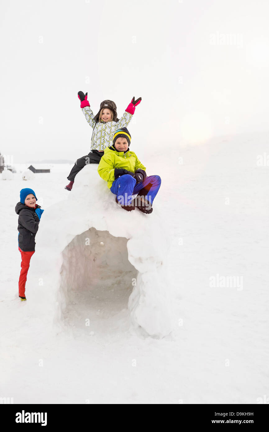 Two children sitting on top of igloo, boy standing beside it - Stock Image