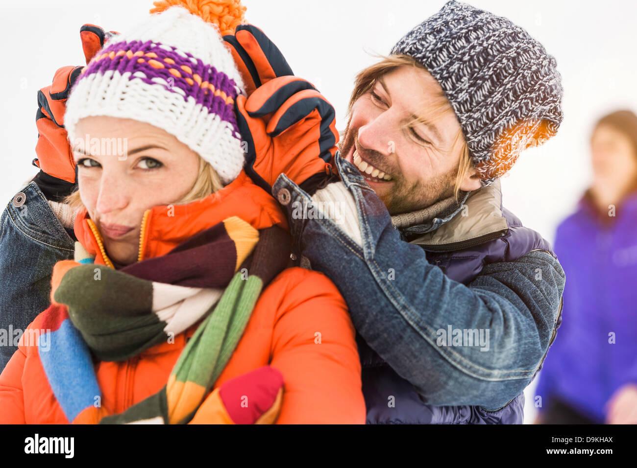 Man making bunny ears behind woman wearing knit hat - Stock Image