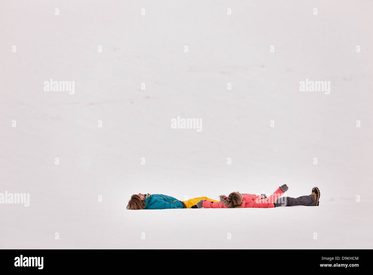 Couple lying on backs in snow - Stock Image