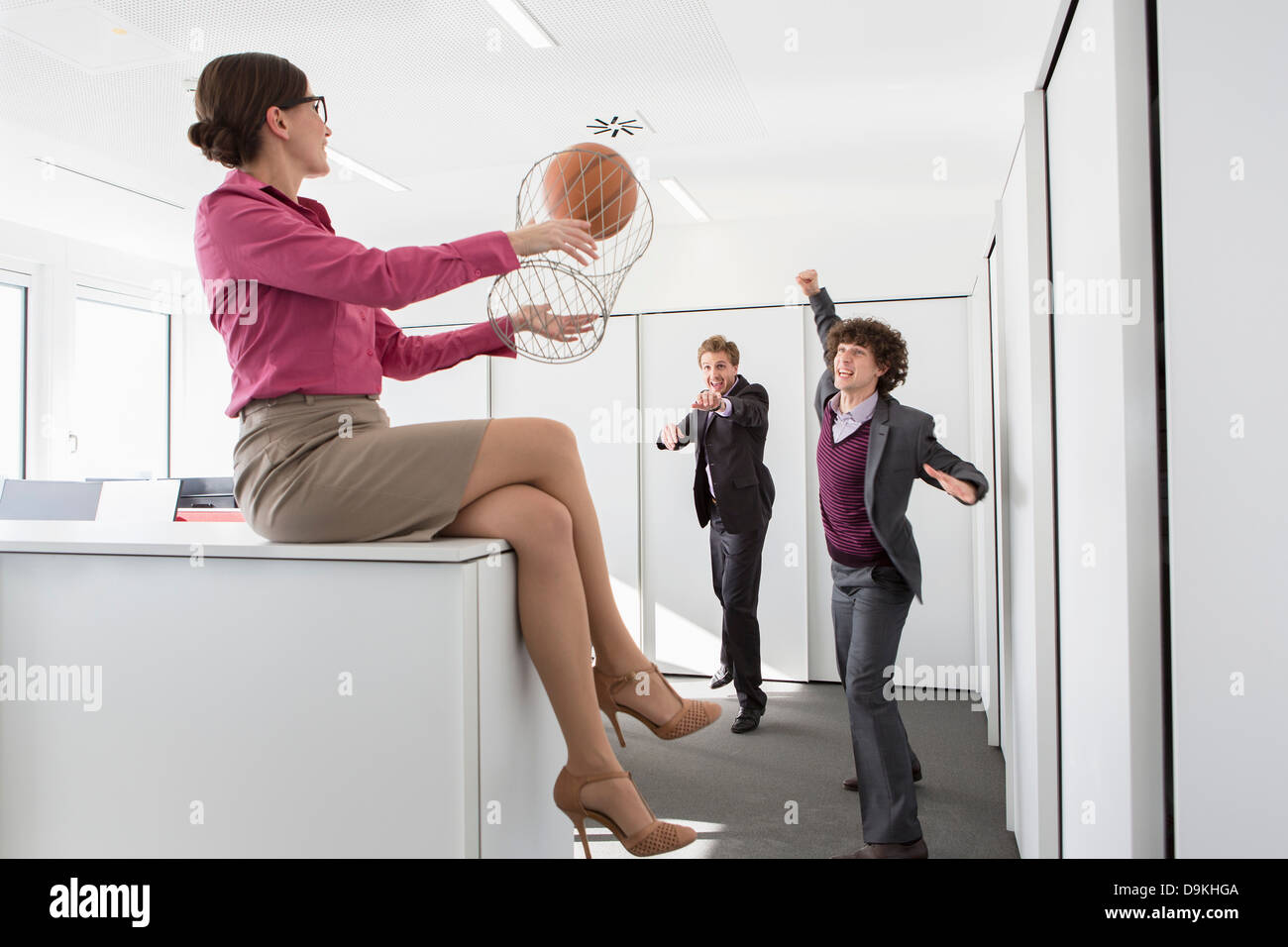 Office workers playing basketball with litter bin - Stock Image