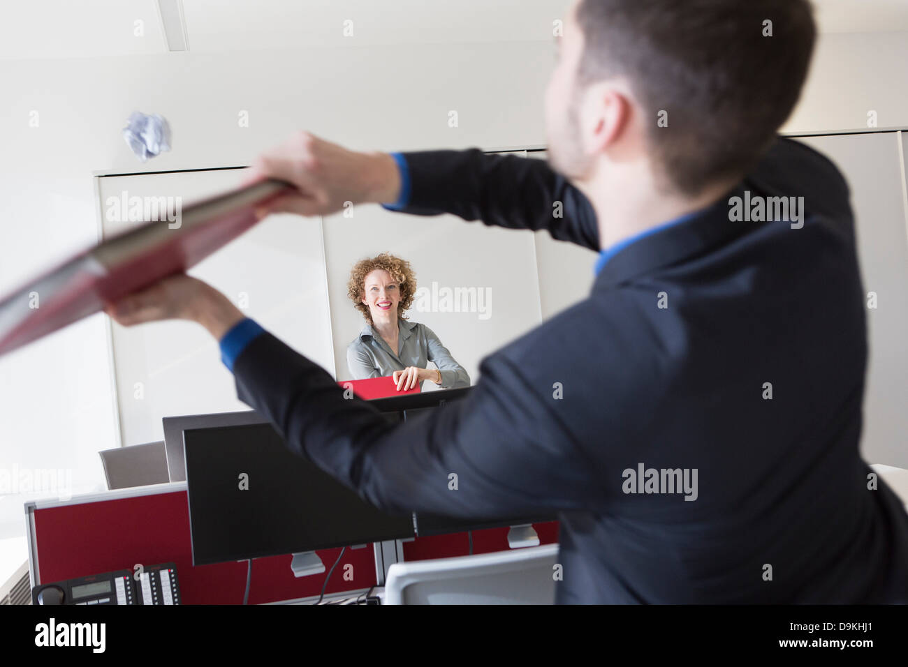 Office worker hitting paper ball with file - Stock Image