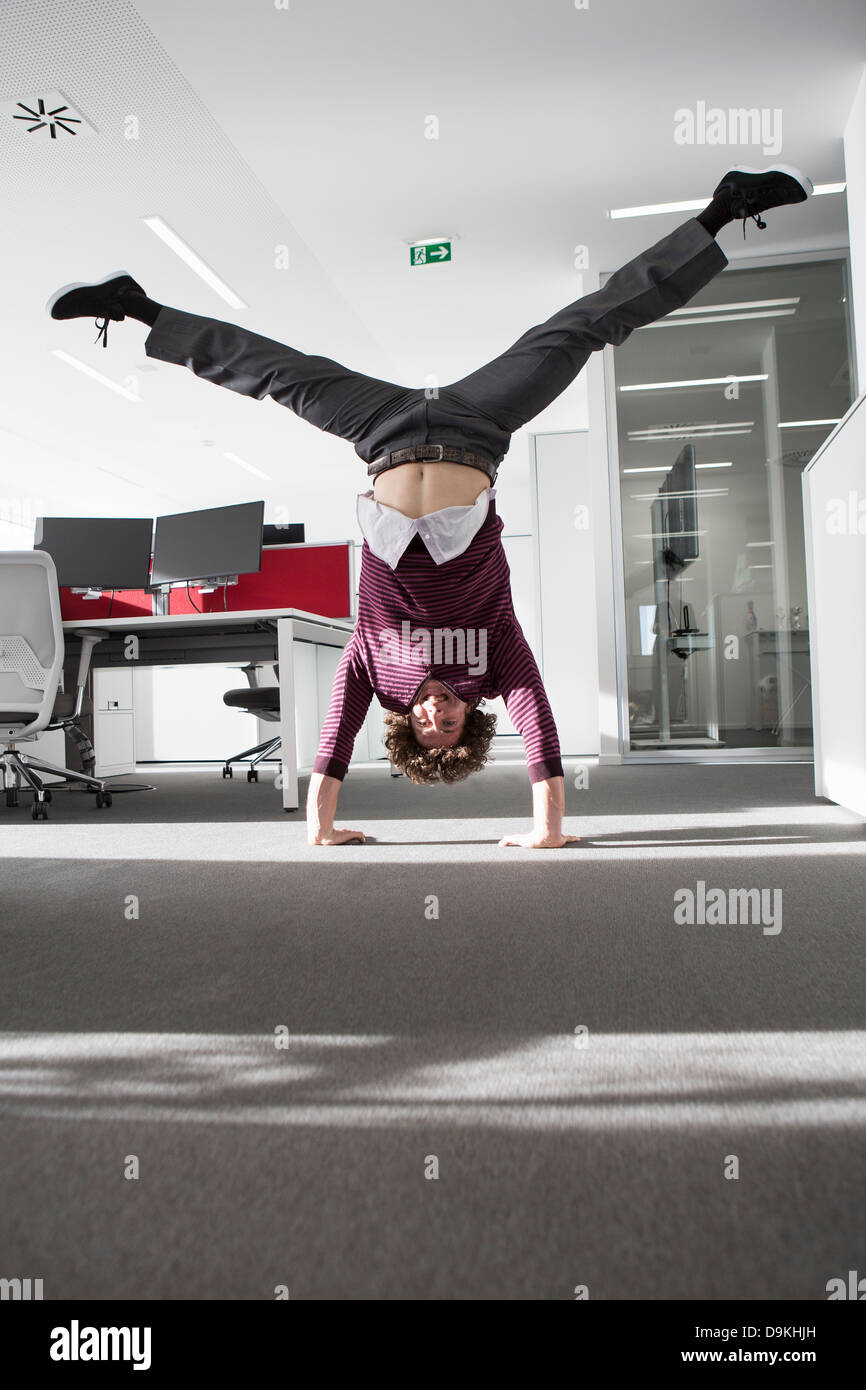 Office worker doing handstand - Stock Image