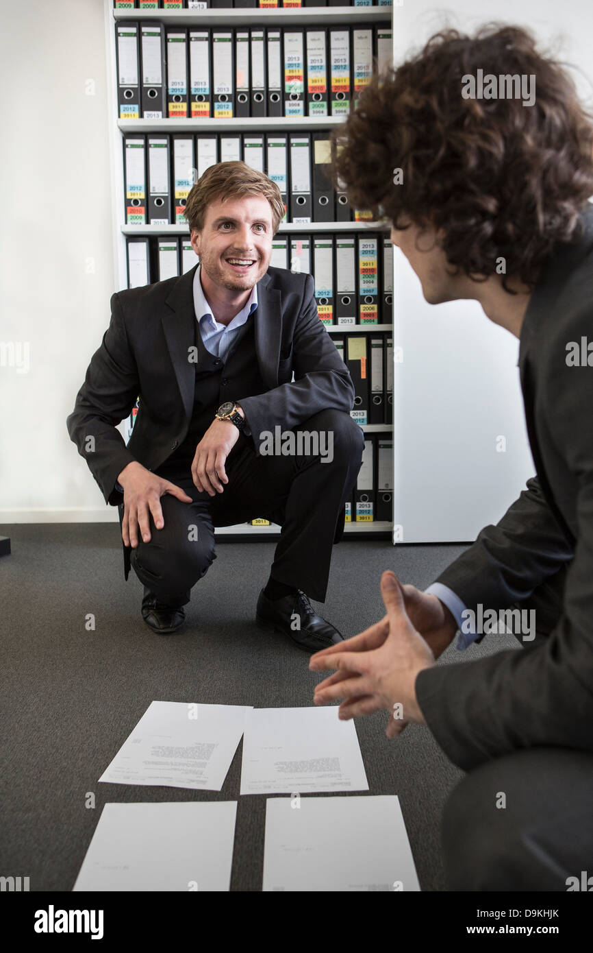 Businessmen laying paperwork on office floor - Stock Image