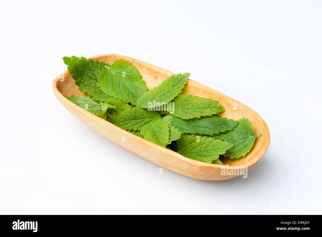 Lemon Balm (Melissa officinalis) Leaves Collected in a Wooden Bowl Stock Photo