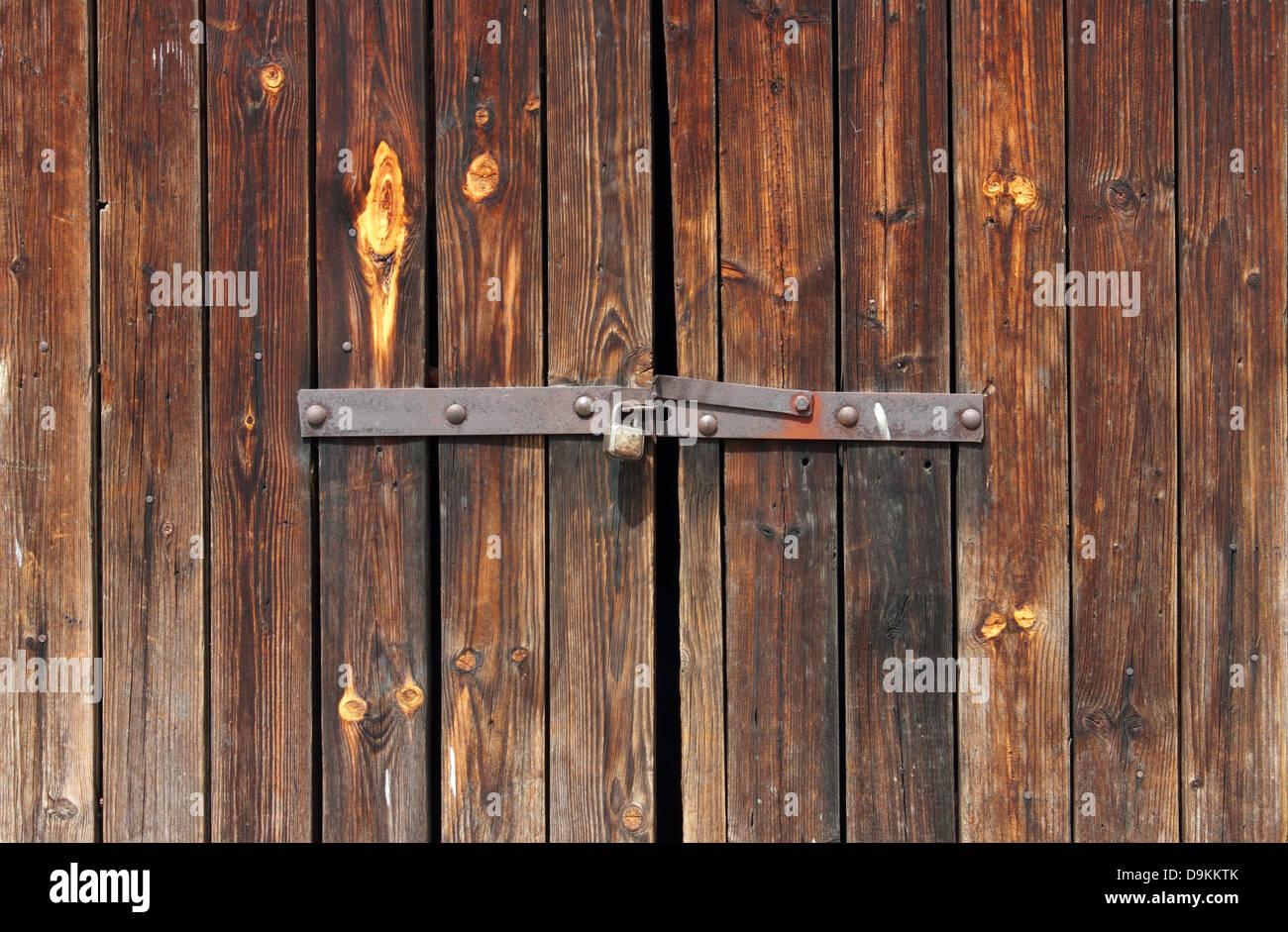 Old Wooden door locked with rusty padlock background. Stock Photo
